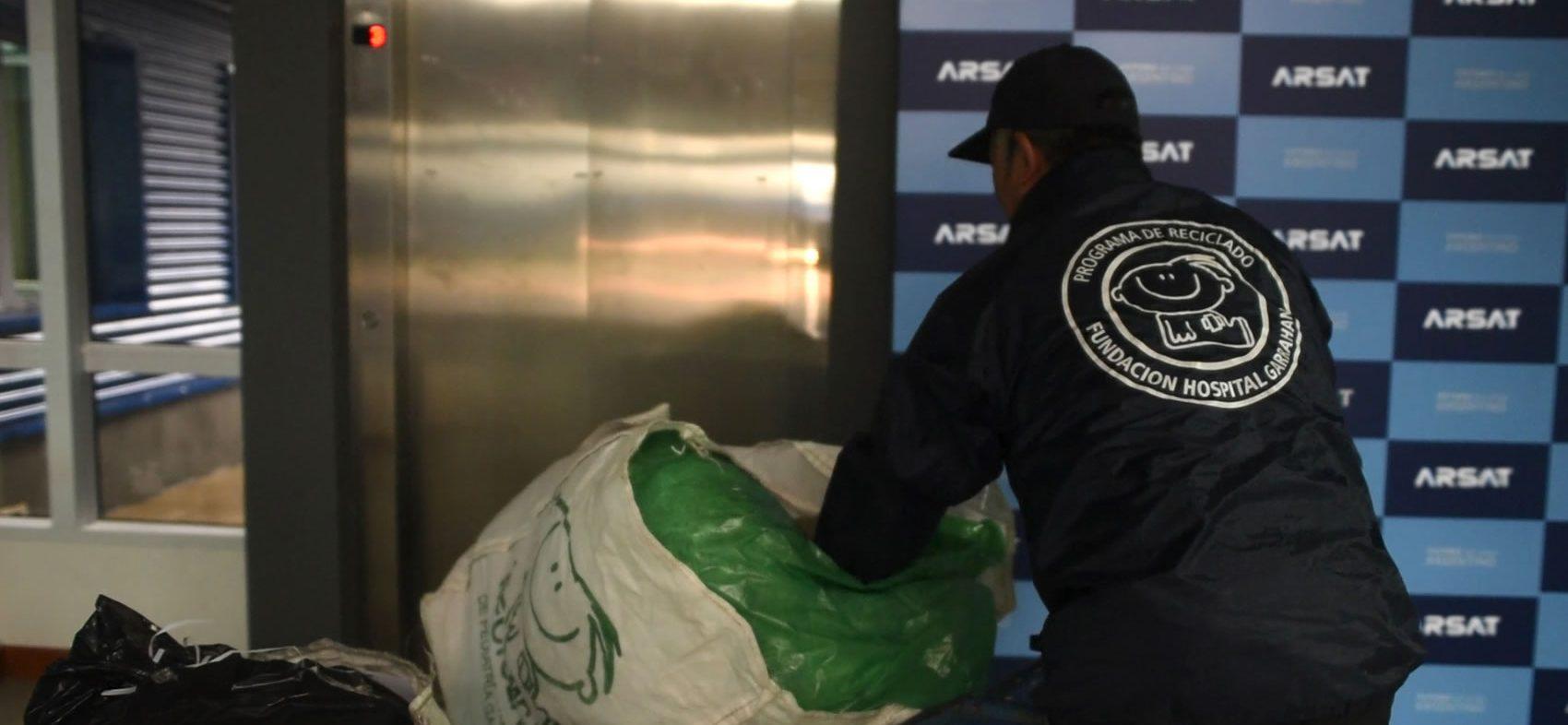 De espaldas, un hombre de la Fundación del Hospital Garraham traslada una bolsa con reciclajes, al fondo se ve un panel con logos de Arsat.