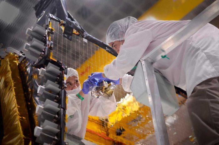 Una ingeniera trabaja minuciosamente sobre el componente de un satélite.