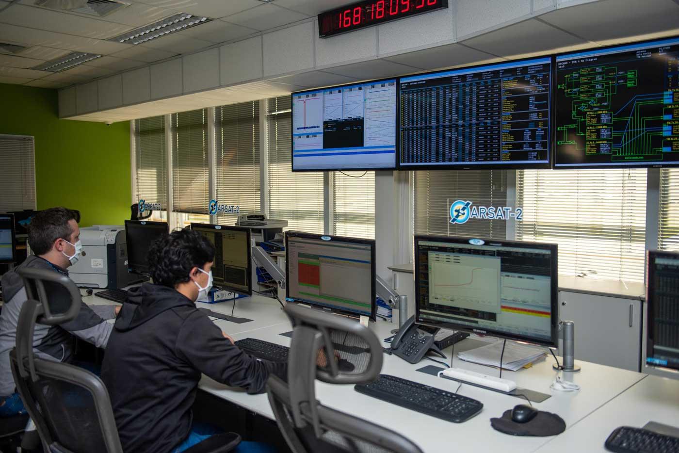 Dos técnicos monitorean y controlan los satélites ARSAT 1 y 2, a través de computadoras en el Centro de Control Satelital.
