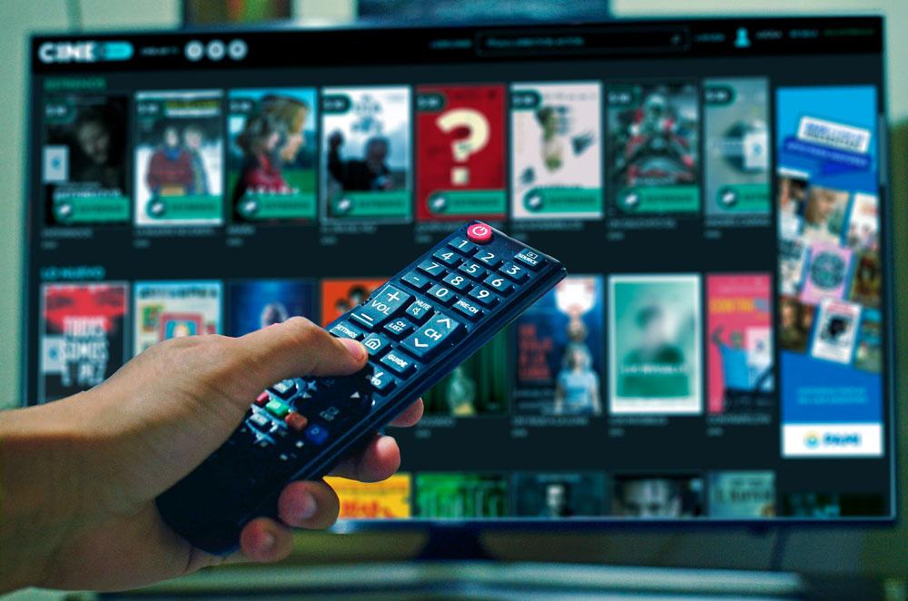 Primer plano de una mano que sostiene un control remoto y apunta hacia un televisor que reproduce Cinear Play.