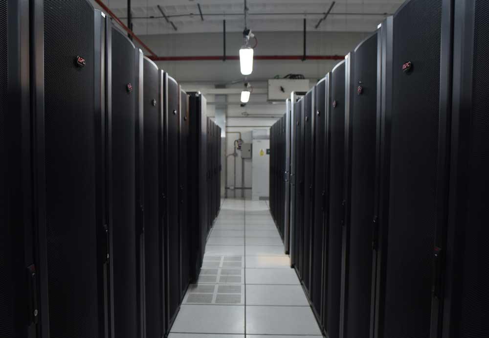 Hileras de racks cerrrados, de color negro, en una sala del Centro Nacional de Datos.