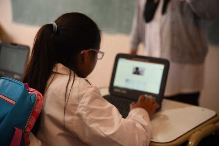 De espalda, una niña con guardapolvo y mochila utiliza una notebook en un pupitre de la escuela.
