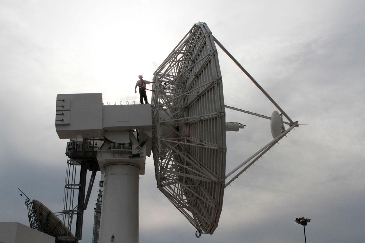 Un ingeniero está a lo alto y por detrás de la antena parabólica mayor, en la Estación Terrena de Benavídez, para trabajos de reacondicionamiento.
