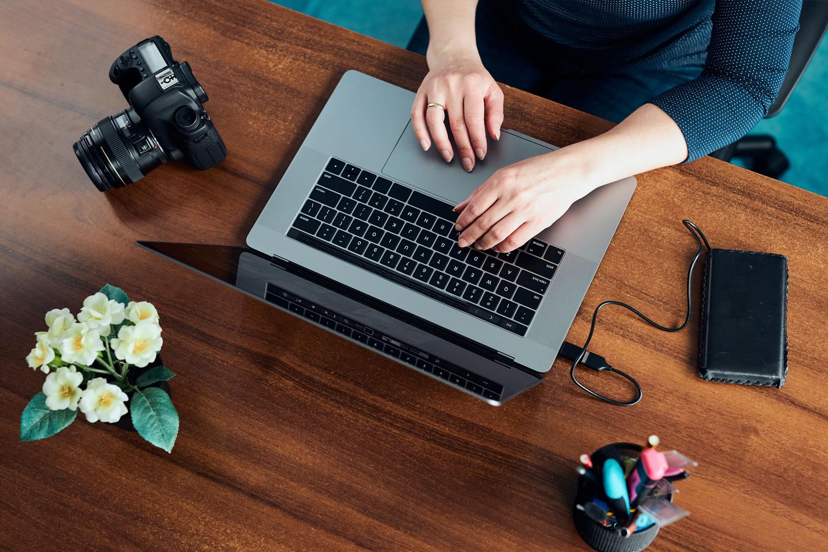 Plano cenital de manos de mujer sobre una Macbook, en su lateral izquierdo hay una cámara reflex y flores blancas y en su derecho, un disco externo.