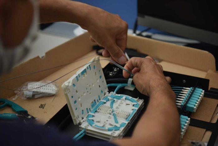 Las manos de un técnico empalman pelos de fibra óptica en un cable de color celeste.