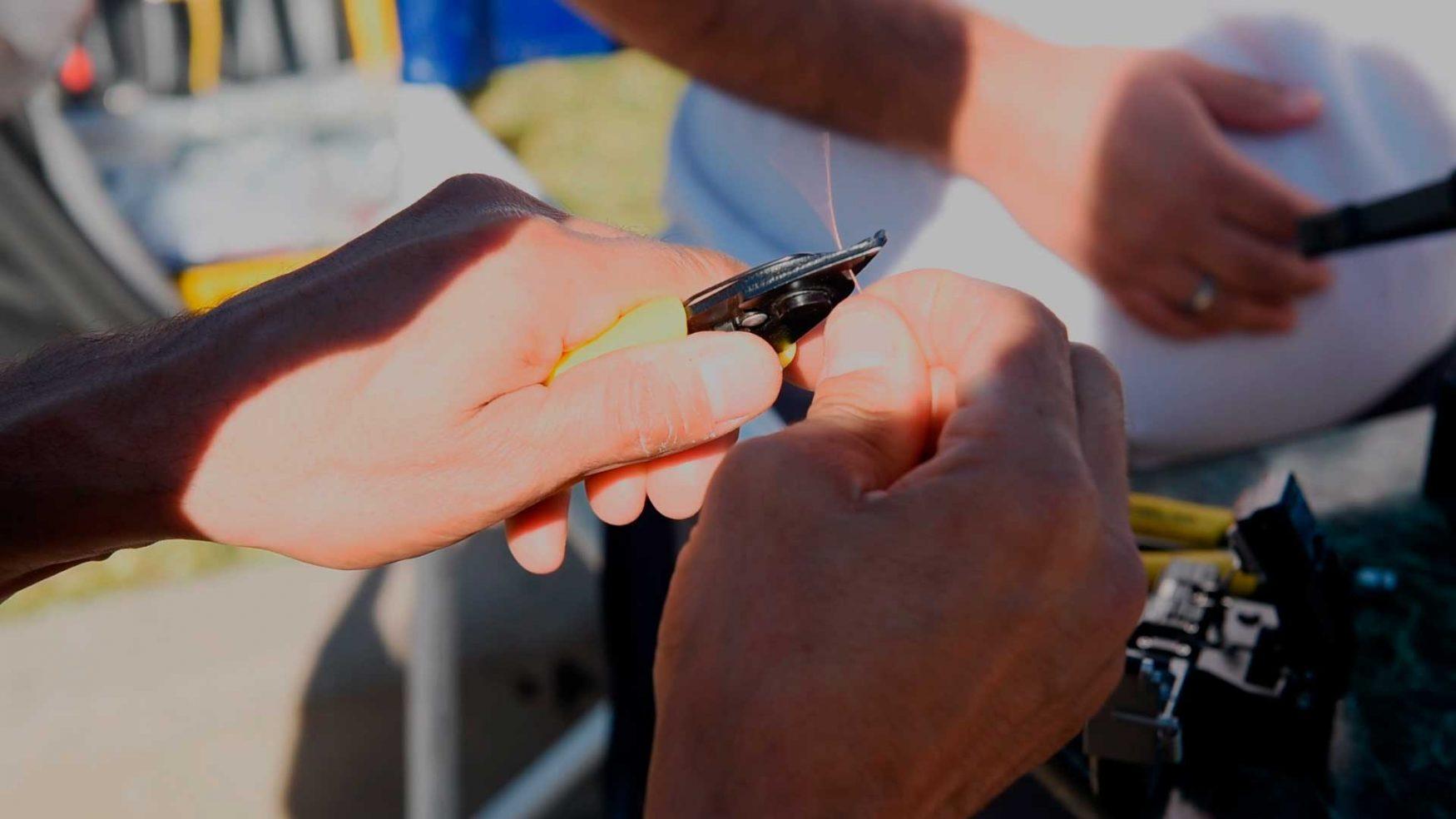 Las manos de un técnico cortan con una pinza un pelo de fibra óptica.
