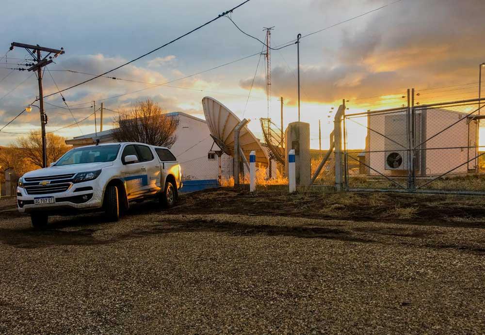Atardecer en la entrada de nodo de la Red Federal de Fibra Óptica. Camioneta blanca de Arsat y dos mojones blancos y celestes.