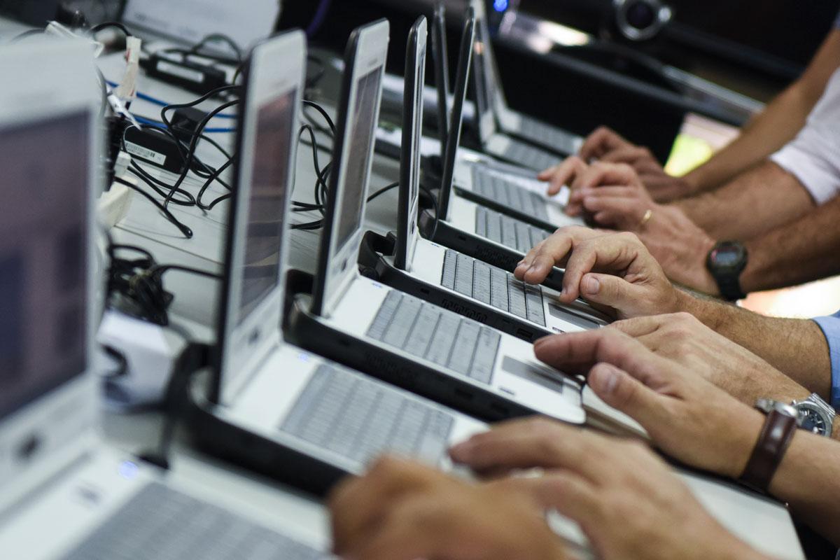 Hilera de las manos de técnicos que tipean en notebooks.