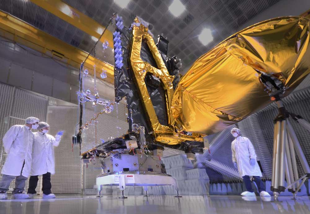 Tres ingenieros observando el cuerpo de un satélite en el Centro de Ensayos de Alta Tecnología Sociedad Anónima CEATSA