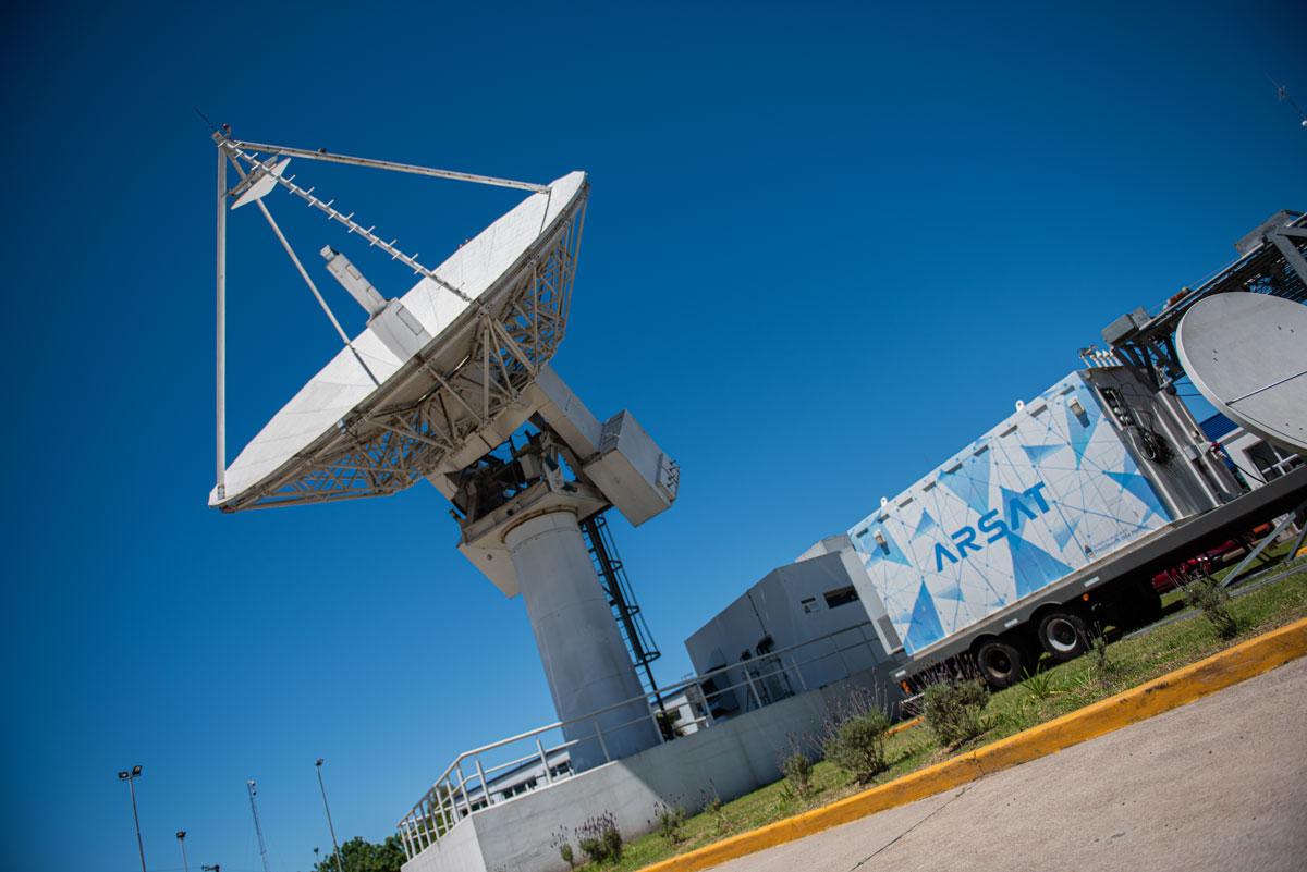 Una gran antena de la Estación Terrena de Benavídez, que apunta hacia el cielo donde están el Arsat 1 y 2, junto a un shelter con el logo de Arsat.
