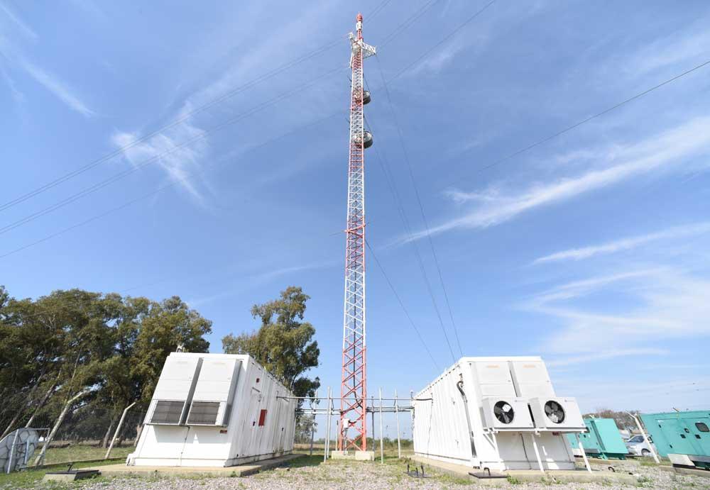 Predio de una Estación Digital de Transmisión, EDT, con dos shelter, dos grupos electrógenos y una extensa torre de telecomunicaciones blanca y roja.