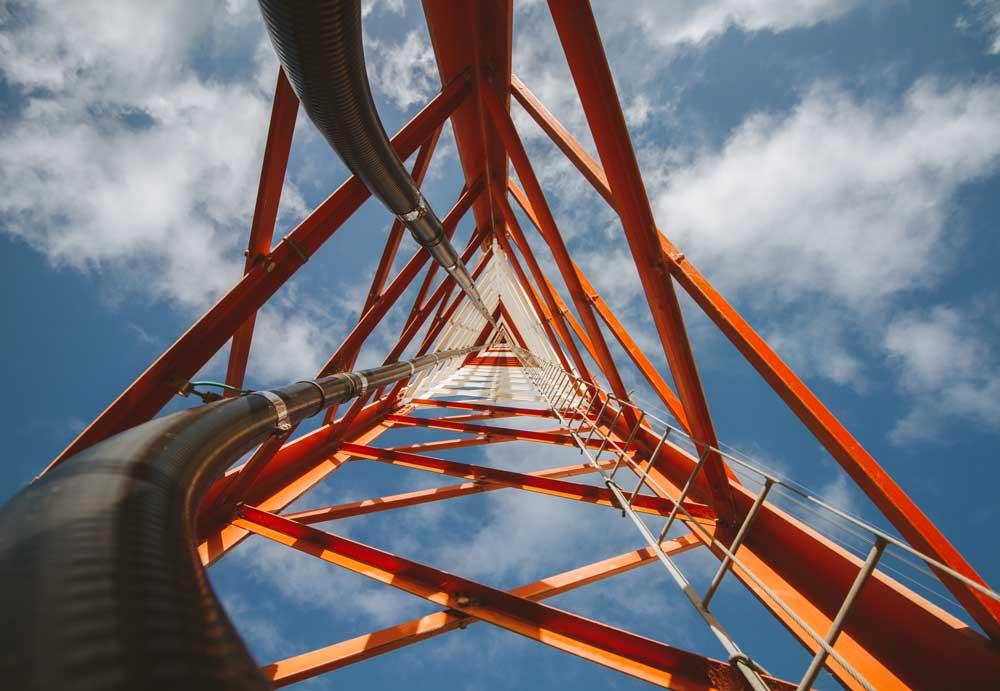 Plano nadir, del interior de una extensa torre de telecomunicaciones de color blanca y roja.