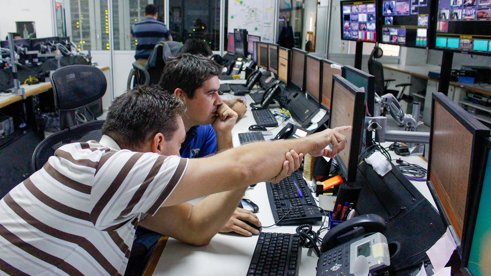 Especialistas en tecnología informática, sentados con auriculares en escritorios compartidos, trabajando con una computadora y 2 pantallas