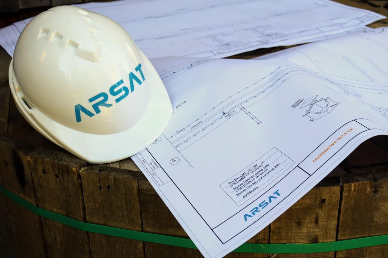 Sobre un barril de madera, hay un casco de seguridad de Arsat y un plano de arquitectura de la red federal de fibra de una cooperativa de un pueblo.