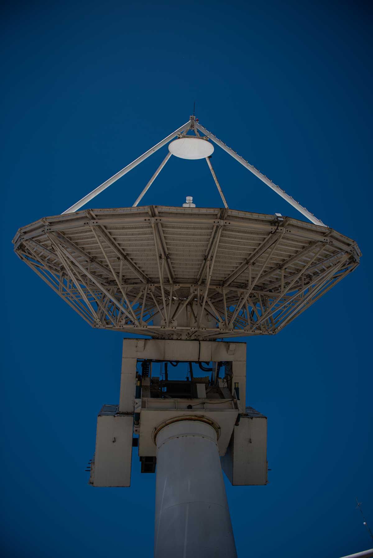 Una gran antena satelital, vista desde abajo, que apunta hacia el cielo donde están el Arsat 1 y 2, para brindar servicio.