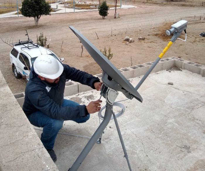 Un técnico instala una antena de internet sobre el techo de un establecimiento en una zona rural.