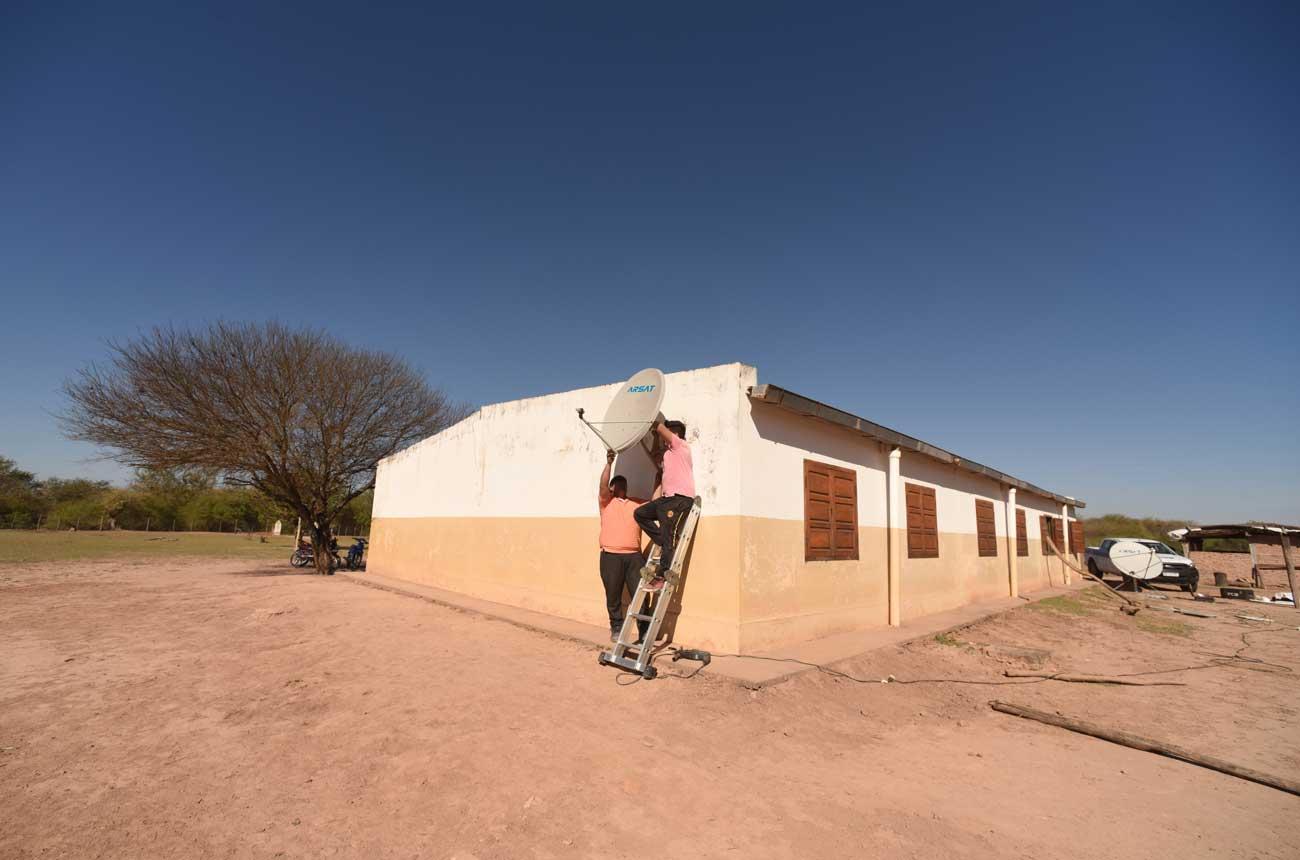 Dos técnicos instalan una antena de internet en una escuela rural.