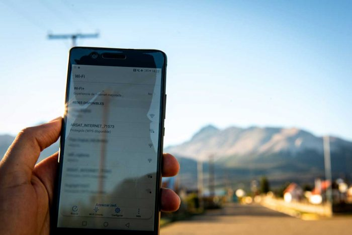 Una mano sostiene un teléfono celular que muestra la red wifi pública de Arsat en un pueblo cordillerano de la Patagonia.