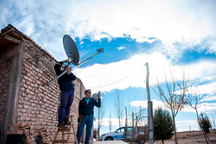 Dos técnicos instalan una antena de internet en un hogar de una zona rural.