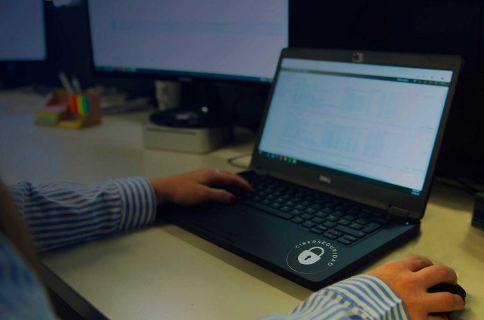 Las manos de un especialista trabajan sobre una notebook que tiene el logo de Ciberseguridad.