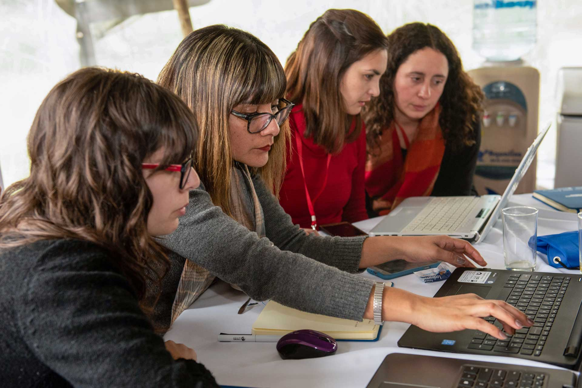 Cuatro mujeres frente a dos notebooks resuelven ejercicios de ciberseguridad.