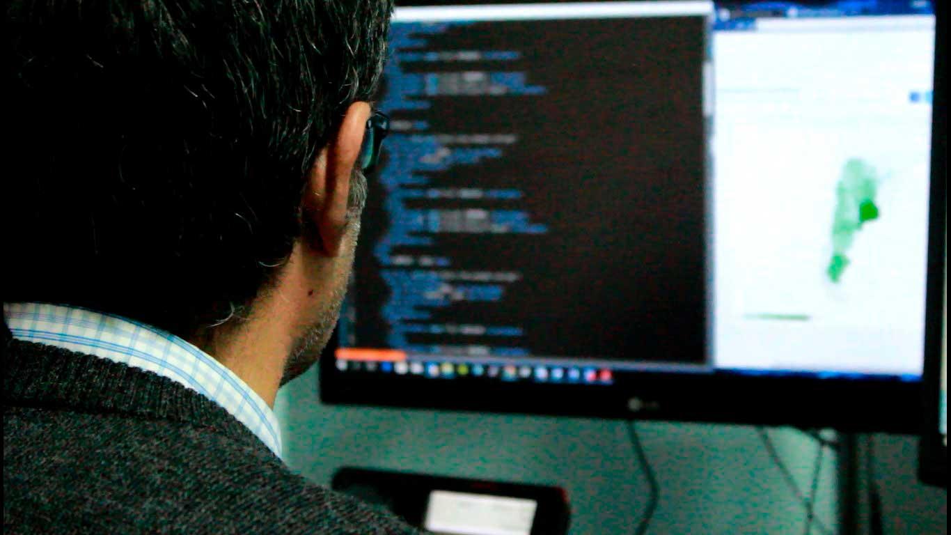 De espalda, un especialista programa en una computadora, sistemas de ciberseguridad.