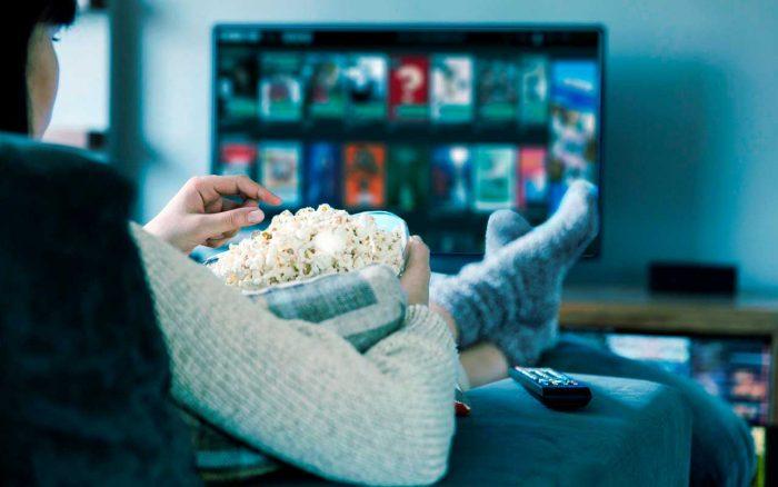 De espaldas, una mujer recostada sobre un sillón, sostiene un balde de pochoclos y mira en un televisor Cinear Play.