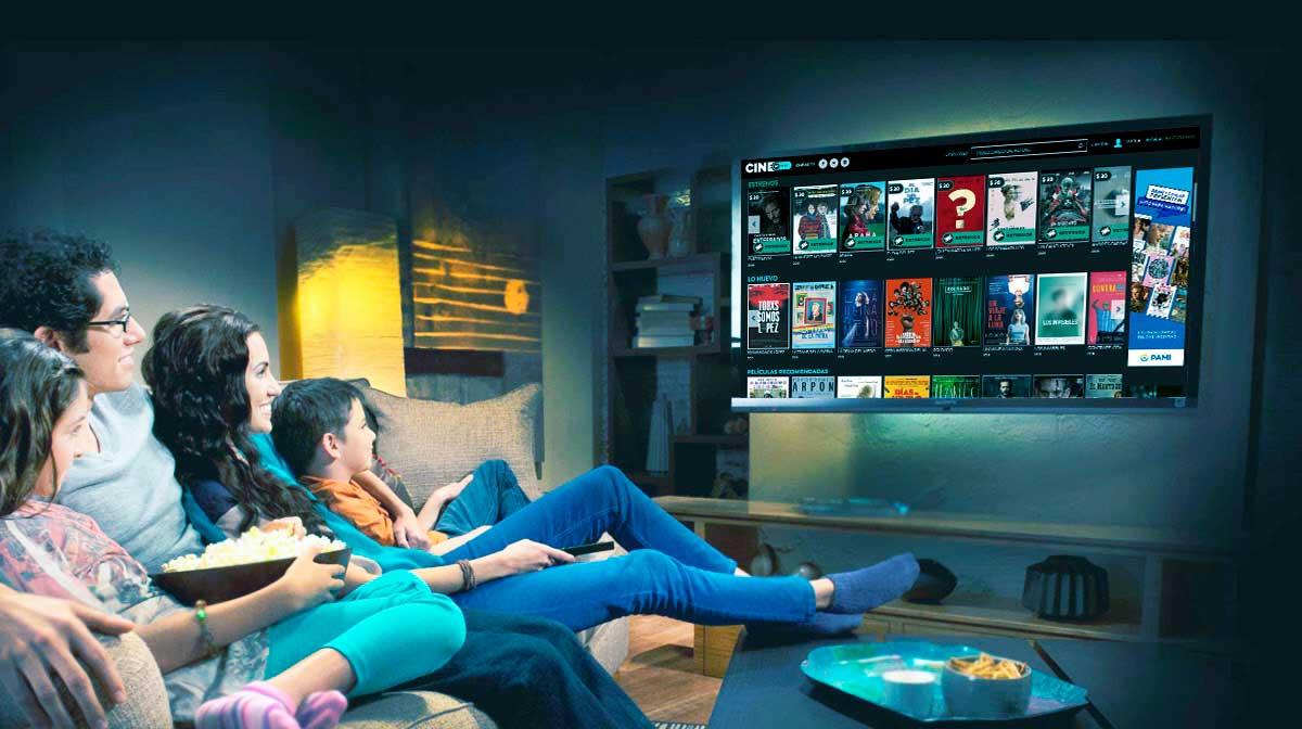 Madre, padre, niño y niña recostados en un sillón, comen pochoclos y miran Cinear Play en un televisor grande colgado en la pared.
