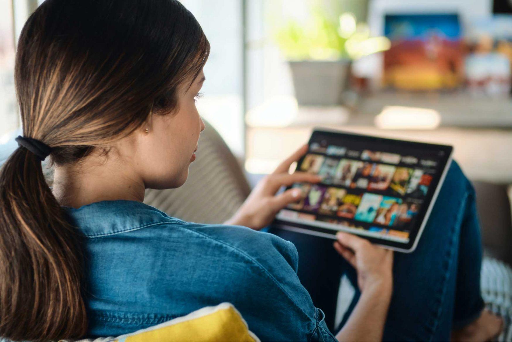 De espaldas, una chica sentada sobre un sillón mira, a través de una tablet, Cinear Play.