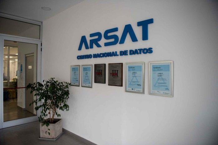 Entrada del Centro Nacional de Datos, en sus paredes está el logo de Arsat y seis cuadros de las certificaciones TIER tres e ISO en inglés y castellano.