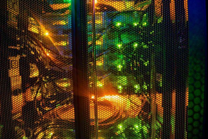 Puerta microperforada de armario rack con cables y luces en una sala del Centro Nacional de Datos.