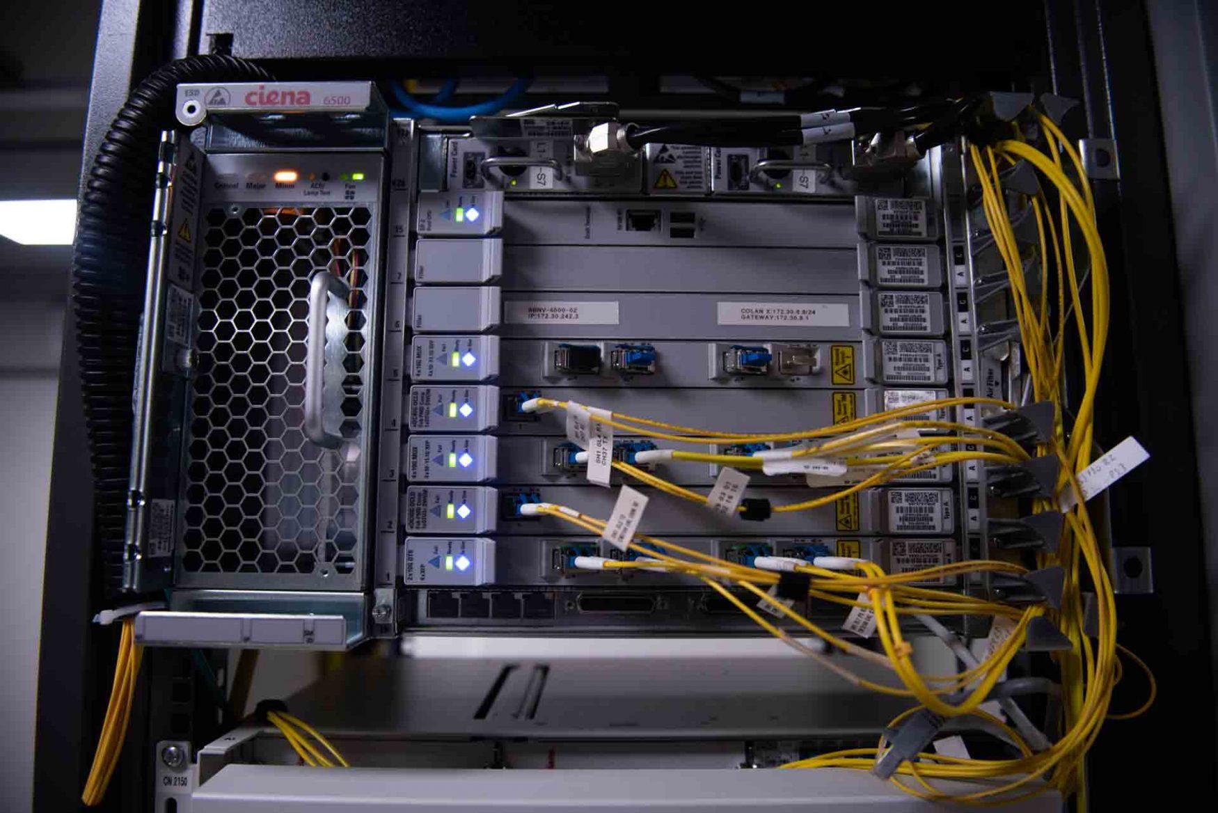 Interior de un rack con luces, entrada de conectores y cables amarillos conectados en una sala del Centro Nacional de Datos.