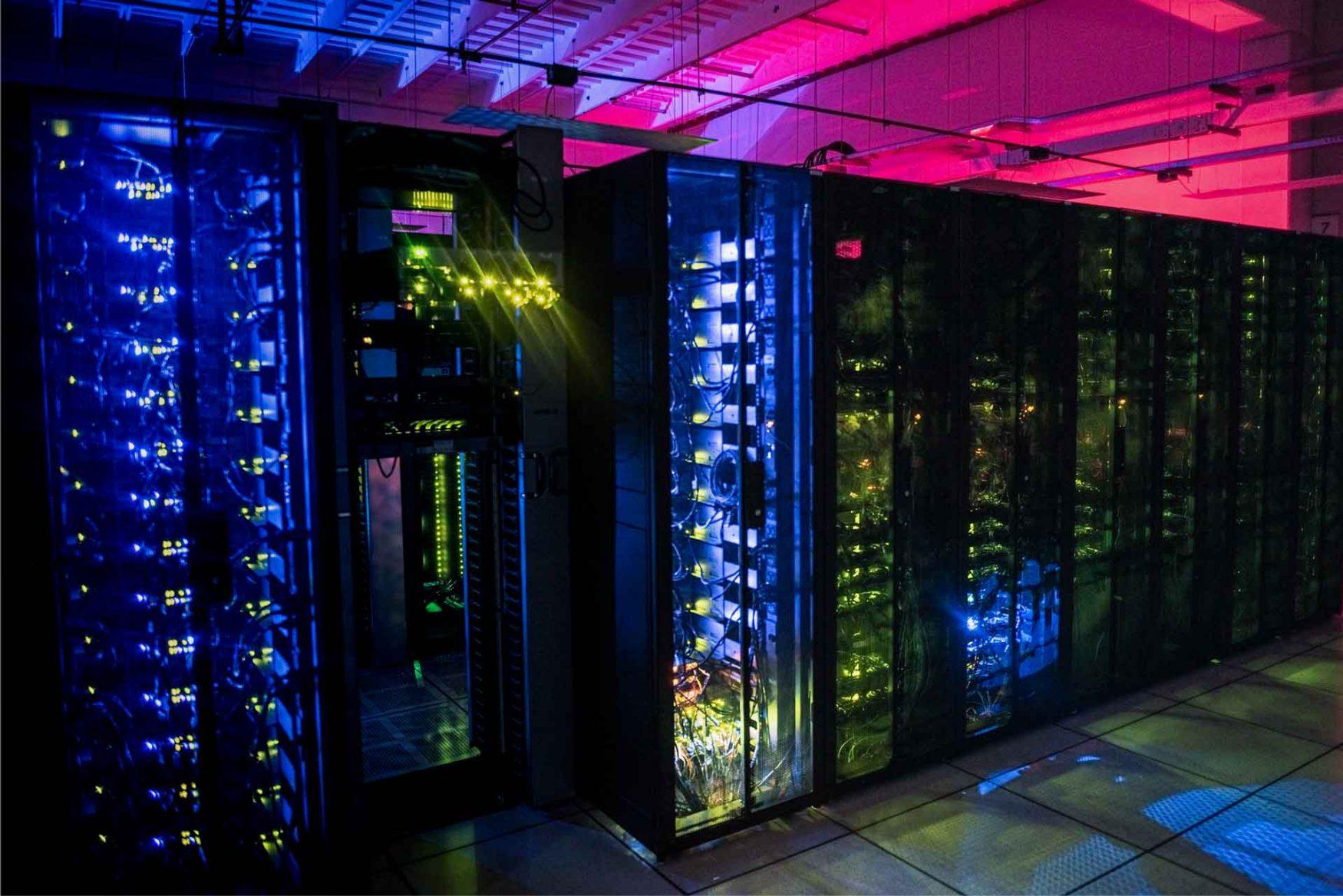 Fila de racks cerrados e iluminados en una sala del Centro Nacional de Datos.