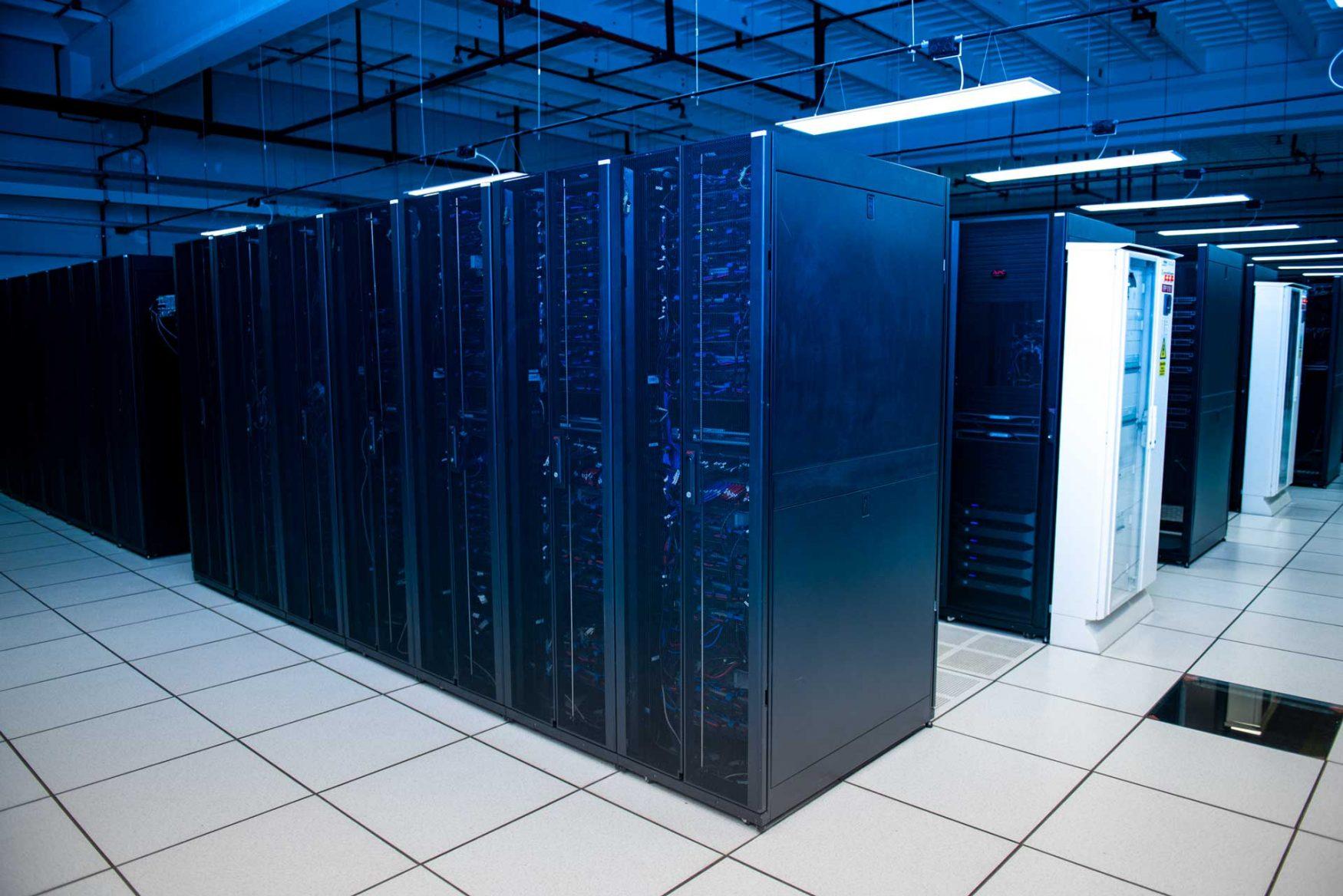 Hilera y filas de racks cerrados e iluminados en una sala del Centro Nacional de Datos.