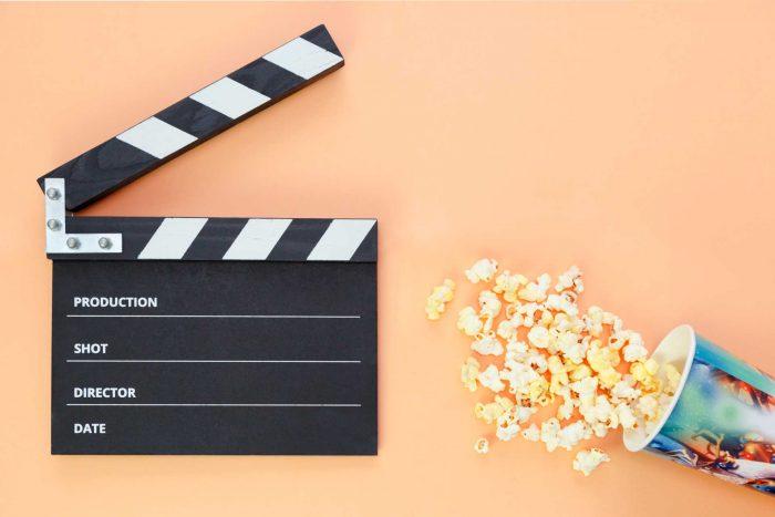 Sobre una superficie naranja, hay una claqueta de cine negra y blanca, y un pequeño balde de pochoclos espacidos.