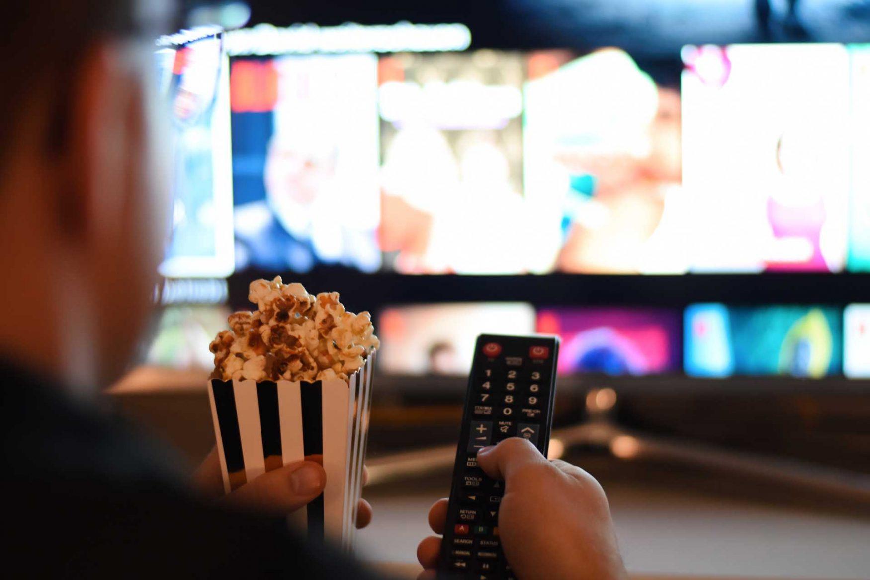 De espaldas, un hombre sostiene con una mano, una porción de pochoclos y en la otra, el control remoto que apunta a un televisor con Cinear Play.