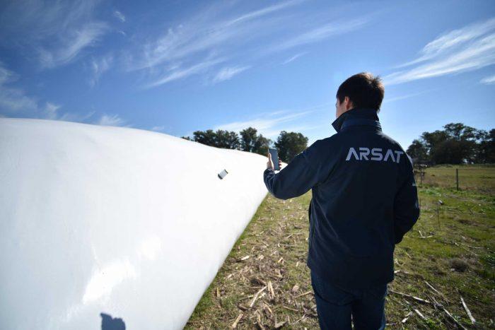 Técnico de espaldas monitorea desde un celular la señal recibida de un dispositivo IOT para recolectar datos de la cosecha dentro de una silobolsa.
