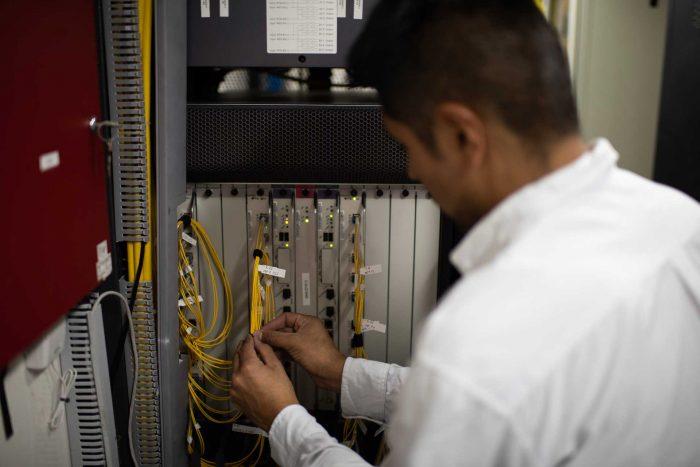 Un técnico de espaldas conecta cables en un equipo de un shelter de la Red Federal de Fibra Óptica.