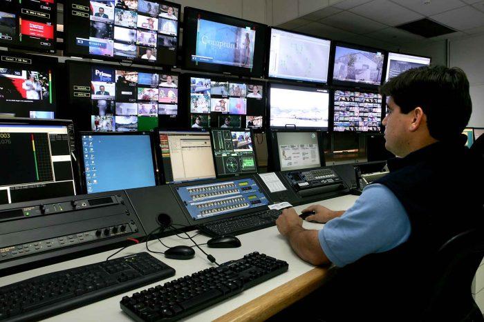 Técnico de espaldas monitorea la transmisión de la Televisión Digital Abierta en el Centro de Operaciones, hay televisores y computadoras.
