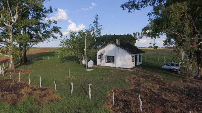 Desde un dron, una escuela rural rodeada de un campo verde. En el piso hay instalada una antena de internet y en la pared una de Televisión digital.