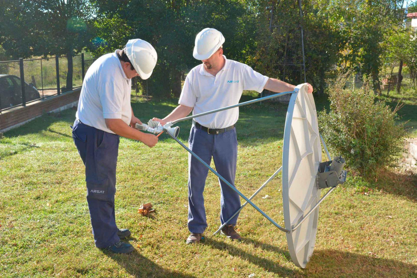 Dos técnicos ajustan una antena de Televisión Digital previo a su instalación.