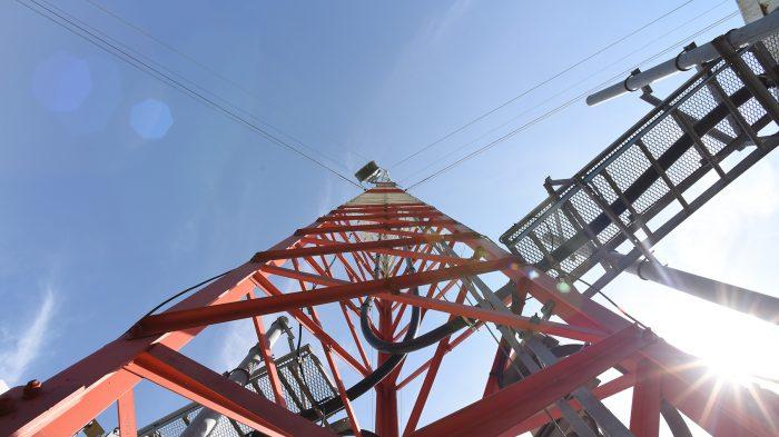 Plano contrapicado de una torre de transmisión de televisión digital, blanca y roja.